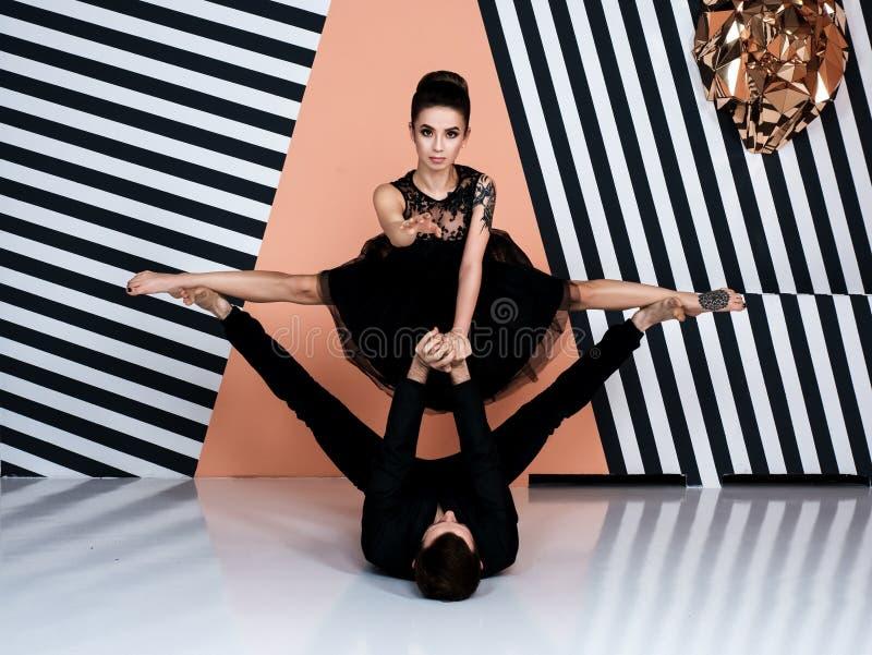 Современные пары артиста балета в черной куртке чернят брюки, черный элемент скачки исполнительского искусства платья с предпосыл стоковое фото