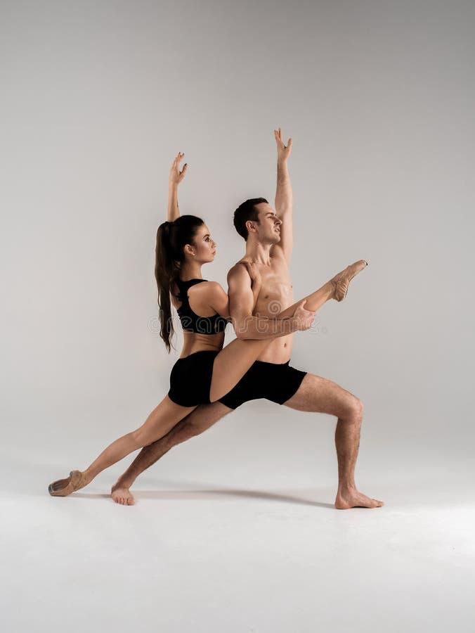 Современные пары артиста балета в черном элементе исполнительского искусства формы с пустым экземпляром размечают izolated предпо стоковые изображения