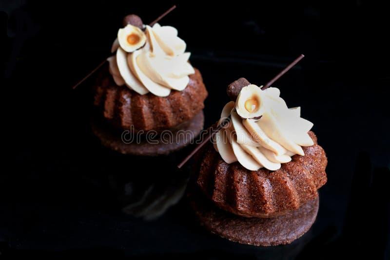 Современные пирожные шоколада с ganache фундука и украшением шоколада на основании печенья шоколада стоковое фото