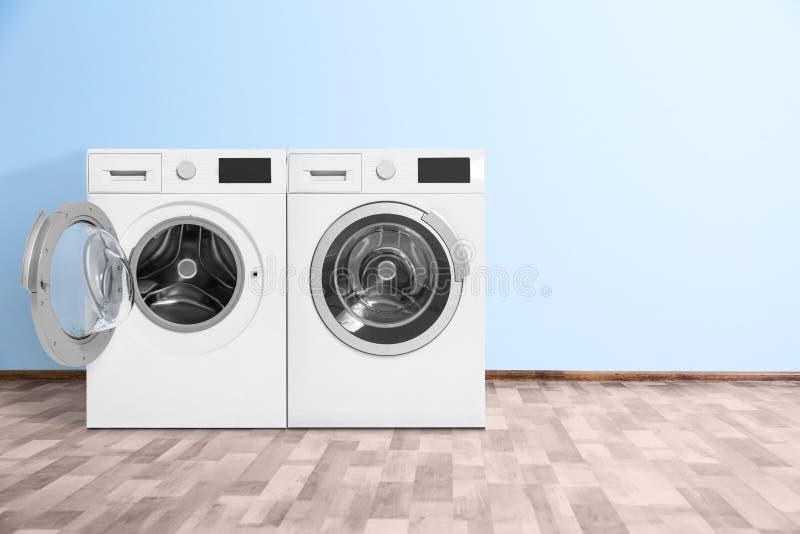 Современные стиральные машины приближают к стене цвета внутри помещения стоковое изображение