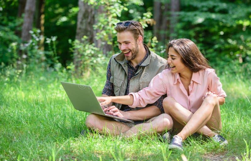 Современные технологии дают возможность быть онлайн и работу во всех условиях окружающей среды Человек и девушка смотря компьтер- стоковое изображение rf