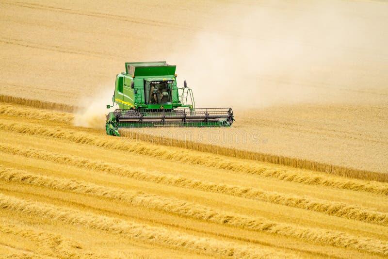 Современные урожаи вырезывания жатки зернокомбайна John Deere стоковое изображение rf