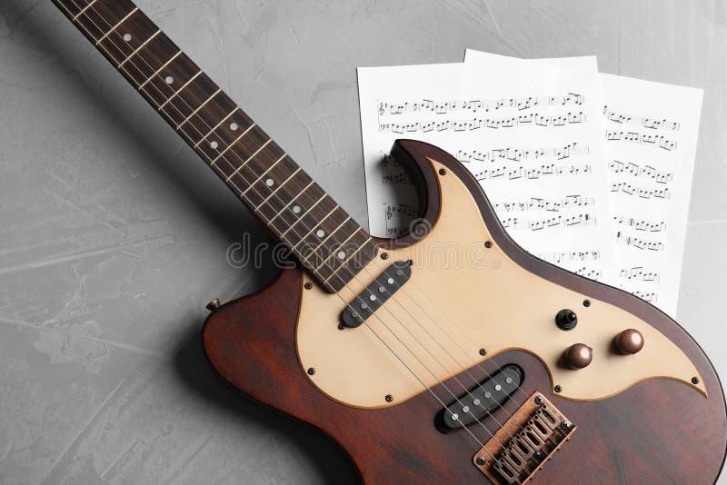 Современные электрическая гитара и листы музыки на предпосылке цвета стоковое изображение