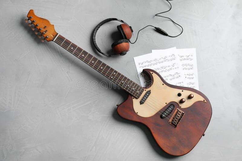 Современные электрическая гитара, наушники и листы музыки на предпосылке цвета стоковая фотография