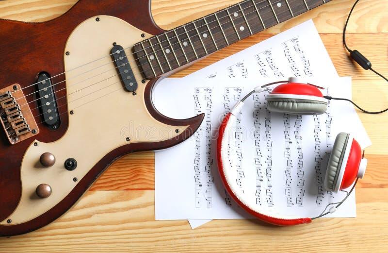 Современные электрическая гитара, наушники и листы музыки на деревянной предпосылке стоковое фото rf