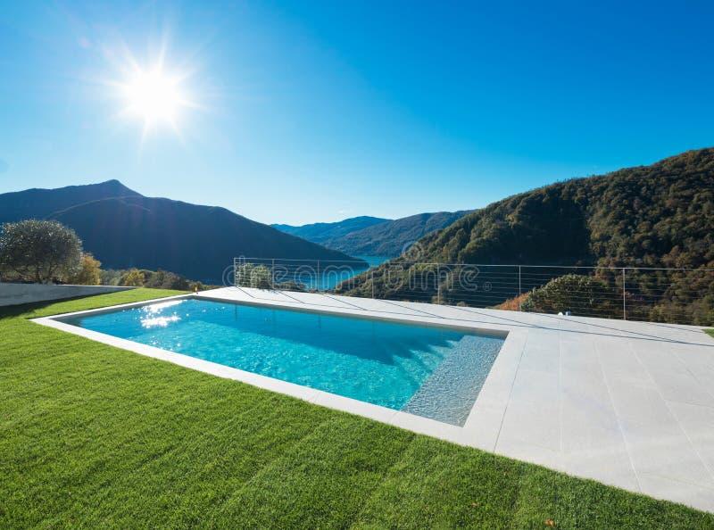 Современный бассейн в саде с взглядом озера и долины стоковое изображение