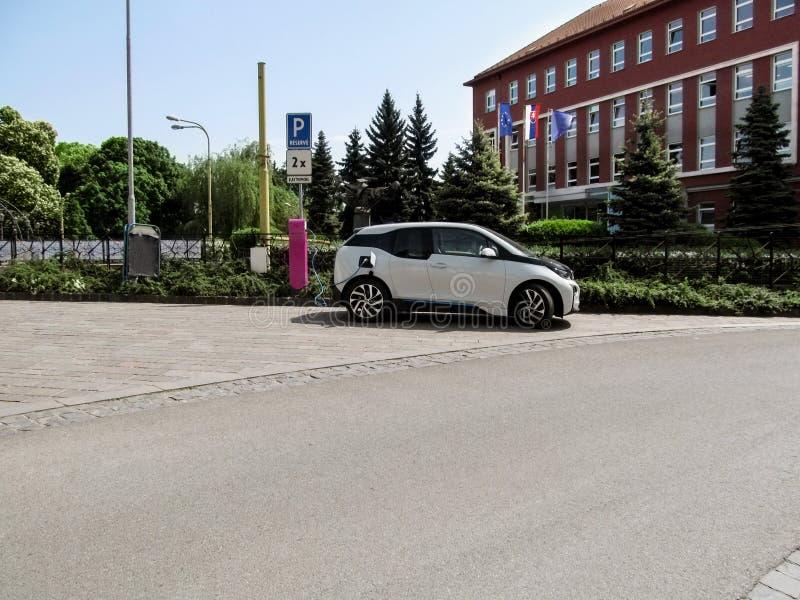 Современный белый электрический автомобиль поручая на улице в Kosice, Словакии Городской пейзаж лета с автомобилем на uncluttered стоковые изображения rf