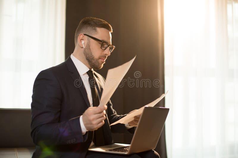 Современный бизнесмен с бумагами и устройствами стоковое фото