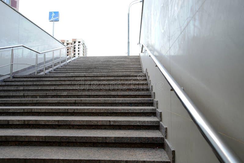 Современный выход из пешеходного тоннеля пуст, вверх по лестницам Лестница до улицы от подземного перехода Нержавеющая сталь стоковая фотография