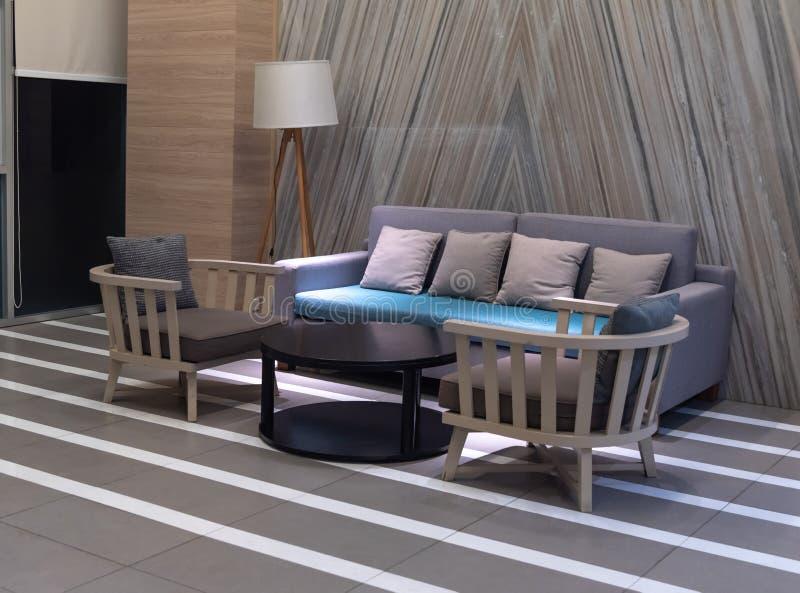 Современный дизайн живущей комнаты с подушками на уютной софе и деревянных лампах с ноутбуком, дизайном интерьера стоковое фото