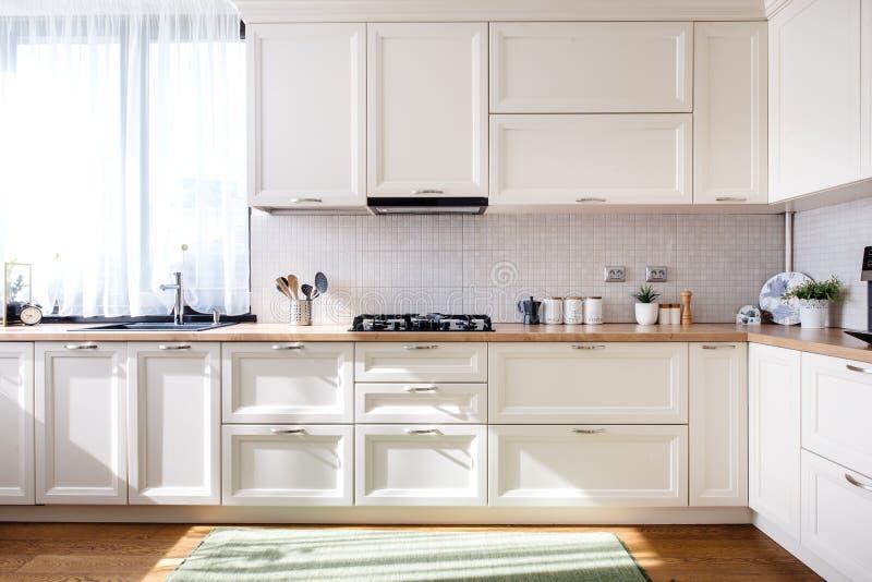 Современный дизайн интерьера кухни с белой мебелью и современные детали стоковое фото