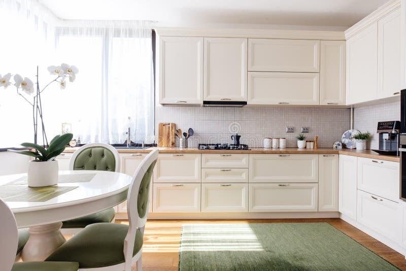 Современный дизайн кухни, красивый интерьер с естественным светом и цветки стоковые фотографии rf