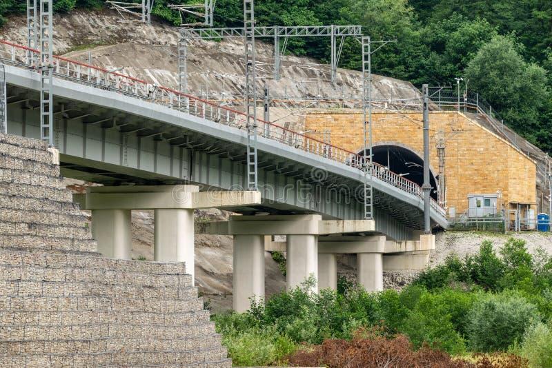 Современный железнодорожный мост водит к тоннелю в горе стоковые фото