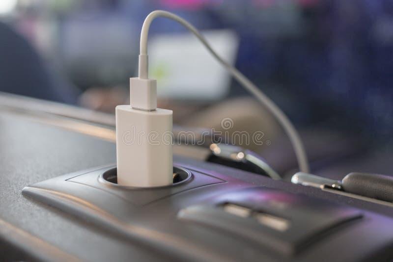 Современный заряжатель мобильного телефона заткнул на электрическом гнезде в авиапорте стоковая фотография