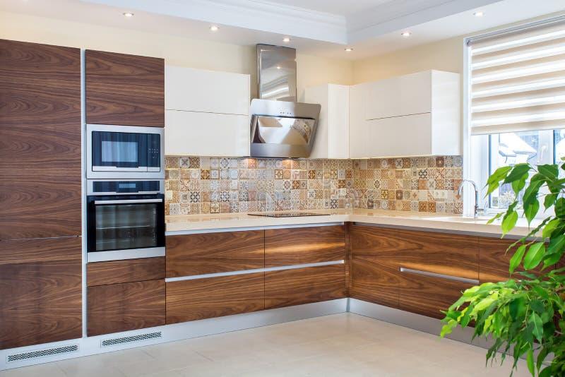 Современный дизайн кухни в свете, яркий интерьер стоковая фотография