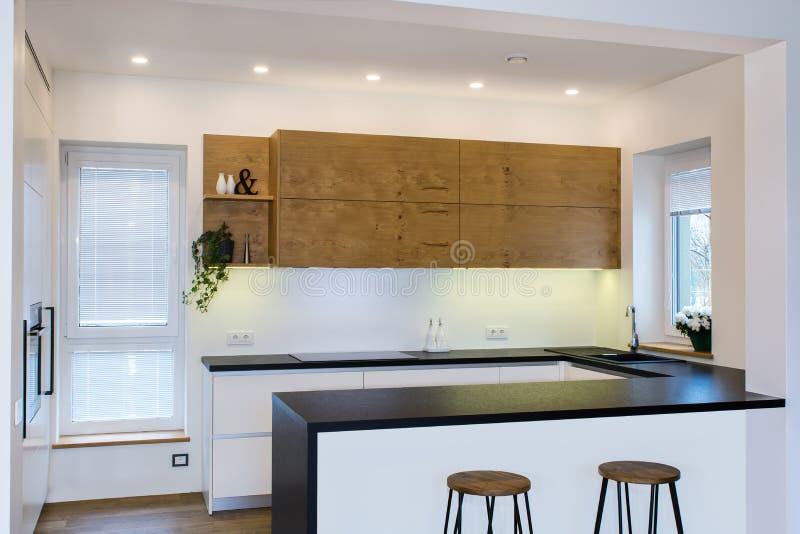 Современный дизайн кухни в светлом интерьере с деревянными акцентами стоковое изображение rf