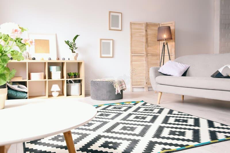 Современный интерьер живущей комнаты с стильной софой стоковое изображение