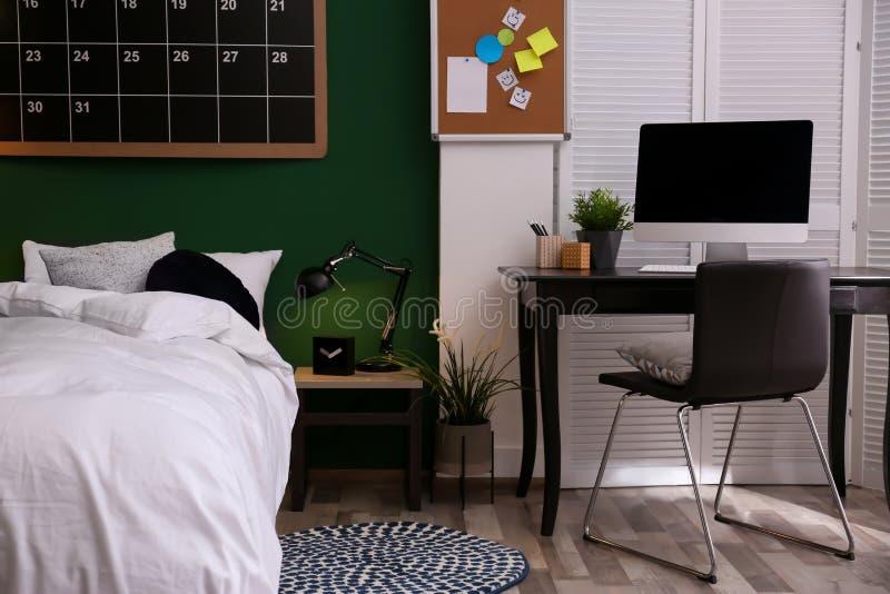 Современный интерьер комнаты подростка с удобной кроватью стоковое изображение rf