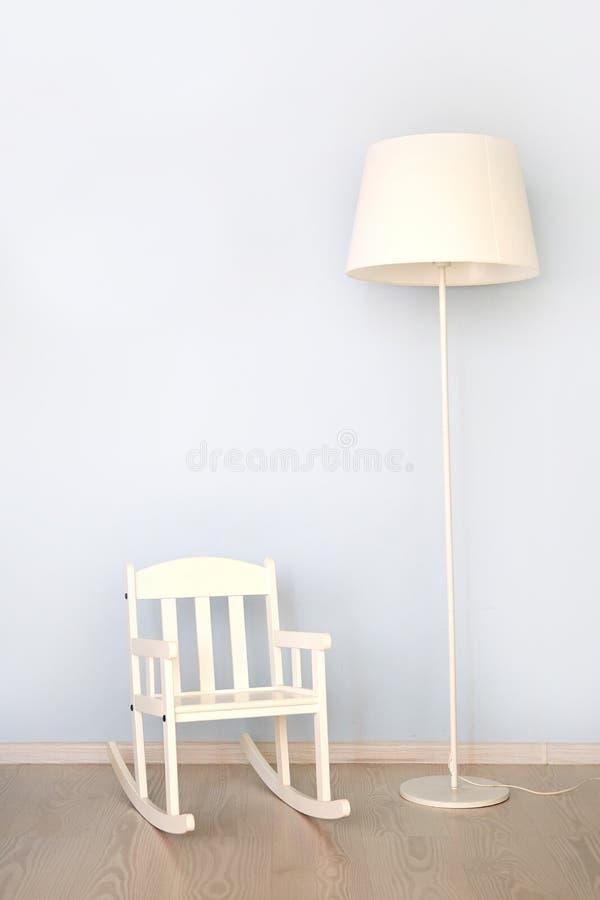Современный интерьер с винтажной лампой и белый стул на деревянном поле против яркой стены стоковое фото