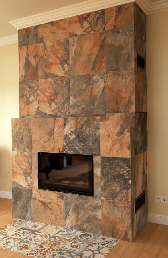 Современный каменный камин в живущей комнате стоковые изображения rf
