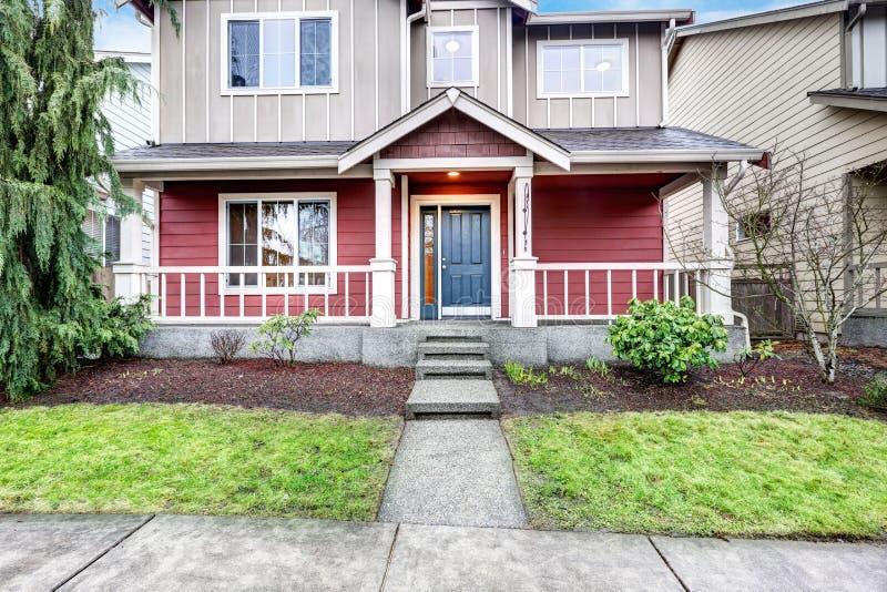 Современный красный и серый домашний экстерьер с крытым крыльцом стоковая фотография