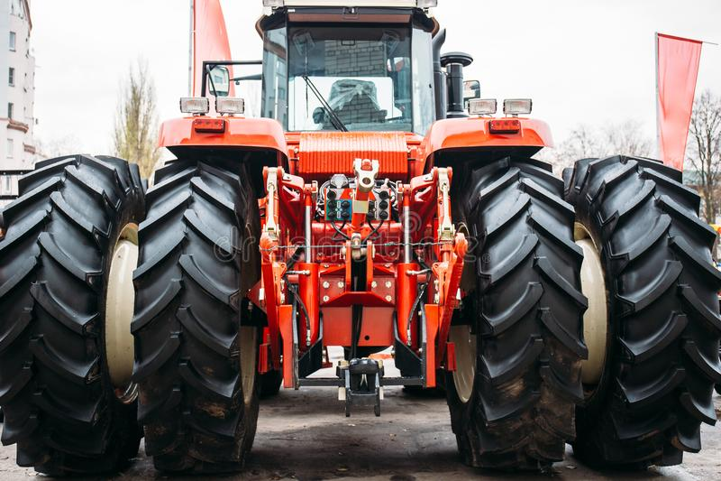 Современный красный трактор с большими колесами, гидравлическая заминка, поднимаясь рамка стоковые фото