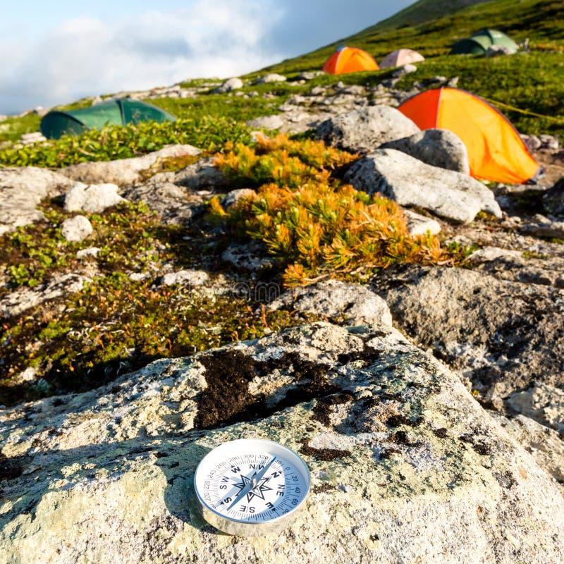Современный круглый компас на камне в тундре около располагаться лагерем шатра Концепция перемещения и активного образа жизни стоковое фото rf