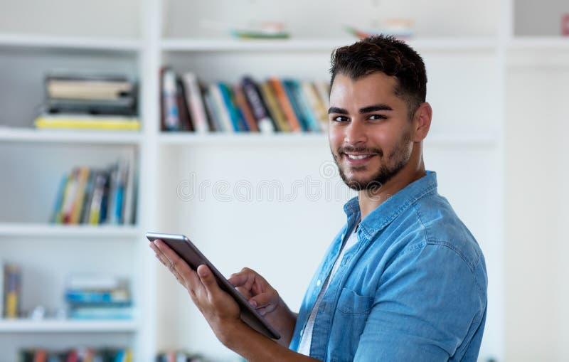 Современный мексиканский человек хипстера работая с планшетом стоковые изображения
