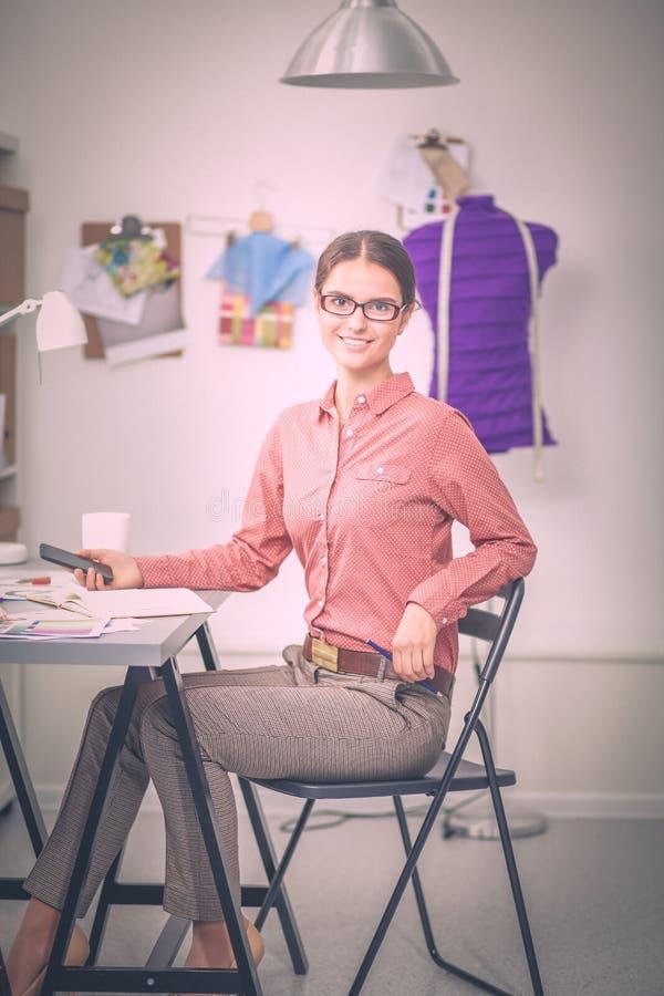 Современный молодой модельер работая на студии стоковое изображение