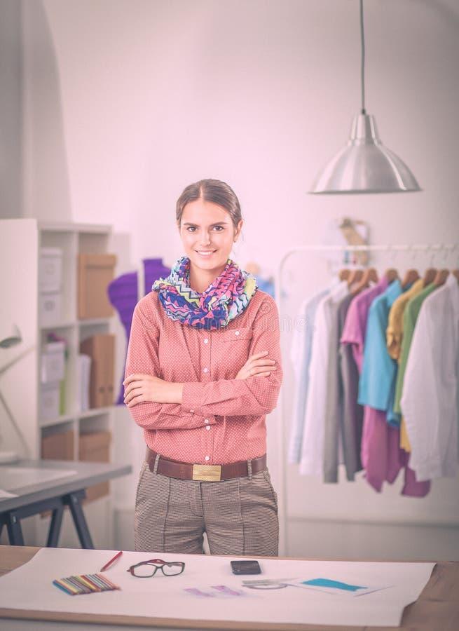 Современный молодой модельер работая на студии стоковое фото