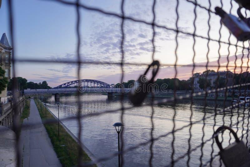 Современный мост в свете захода солнца, покрашенном небе и облаках, заходе солнца рекой, воде города выравнивать прогулку, прогул стоковое изображение