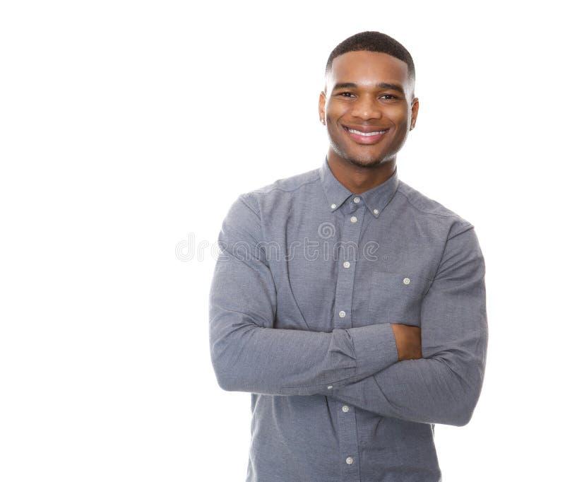 Современный молодой чернокожий человек усмехаясь при пересеченные оружия стоковые изображения