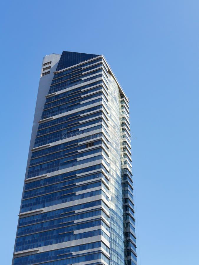 Современный небоскреб со стеклянным фасадом и белые нашивки против голубого неба, вертикального стоковое фото rf