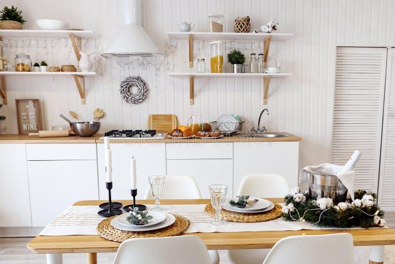 Современный новый светлый интерьер кухни с белыми мебелью и обеденным столом стоковое фото rf