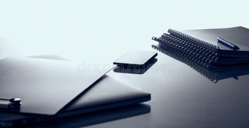 Современный домашний офис с компьютером и компьтер-книжкой, папкой, телефоном лежа на столе стоковое фото