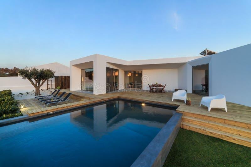 Современный дом с бассейном сада и деревянной палубой стоковое фото