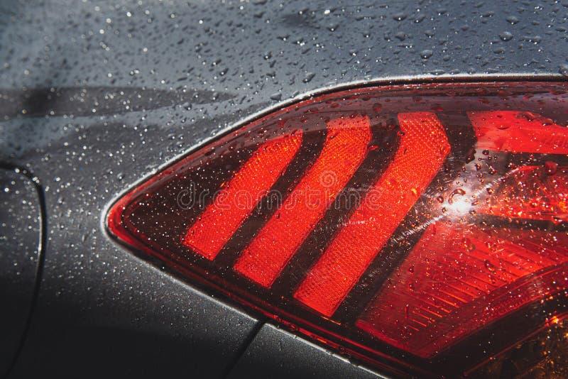 Современный осветите контржурным светом автомобиля после дождя с дождевыми каплями стоковое фото rf