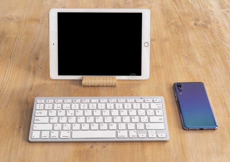 Современный планшет с черным экраном и белый смартфон клавиатуры и дизайна с тройной камерой, в светлой деревянной таблице стоковые фото