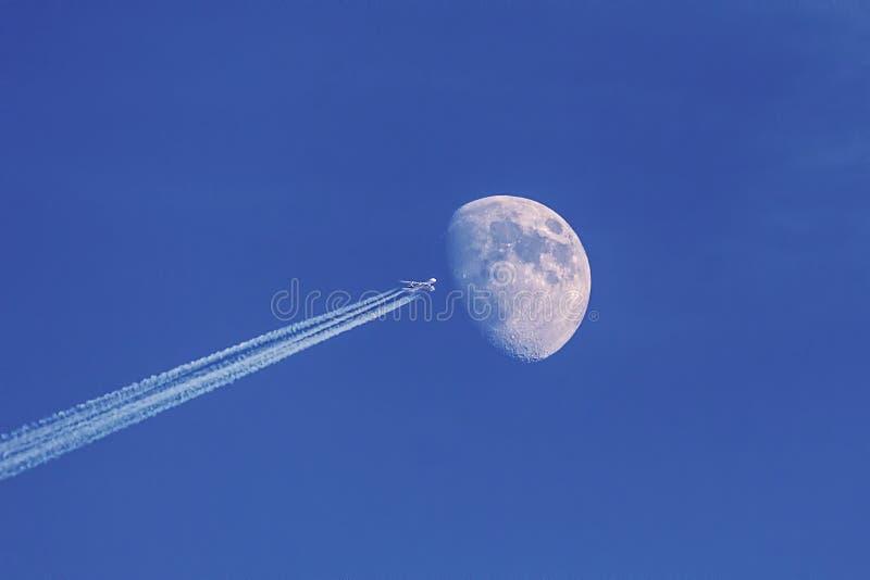 Современный реактивный самолет с луной на голубом небе как предпосылка стоковые изображения