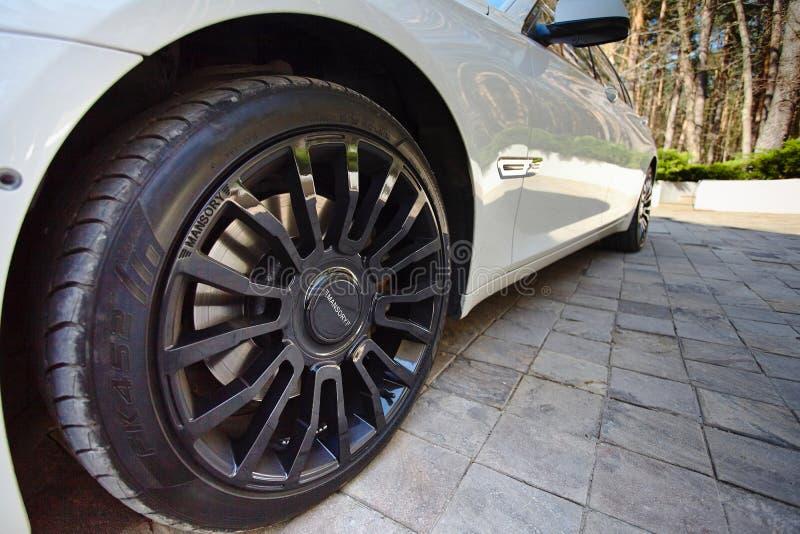 Современный роскошный автомобиль BMW 750Li XDrive припаркованный на каменной вымощенной стоянке с концом-вверх колес сплава черно стоковая фотография rf