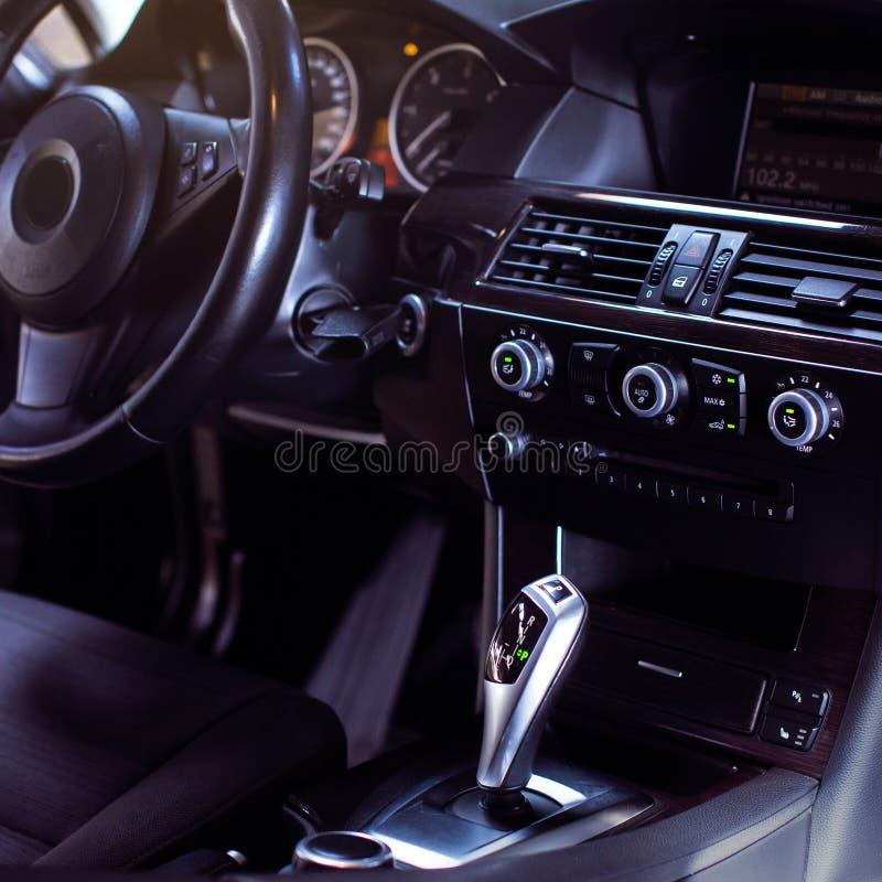 Современный роскошный интерьер автомобиля - рулевое колесо, рычаг переноса и приборная панель стоковое изображение