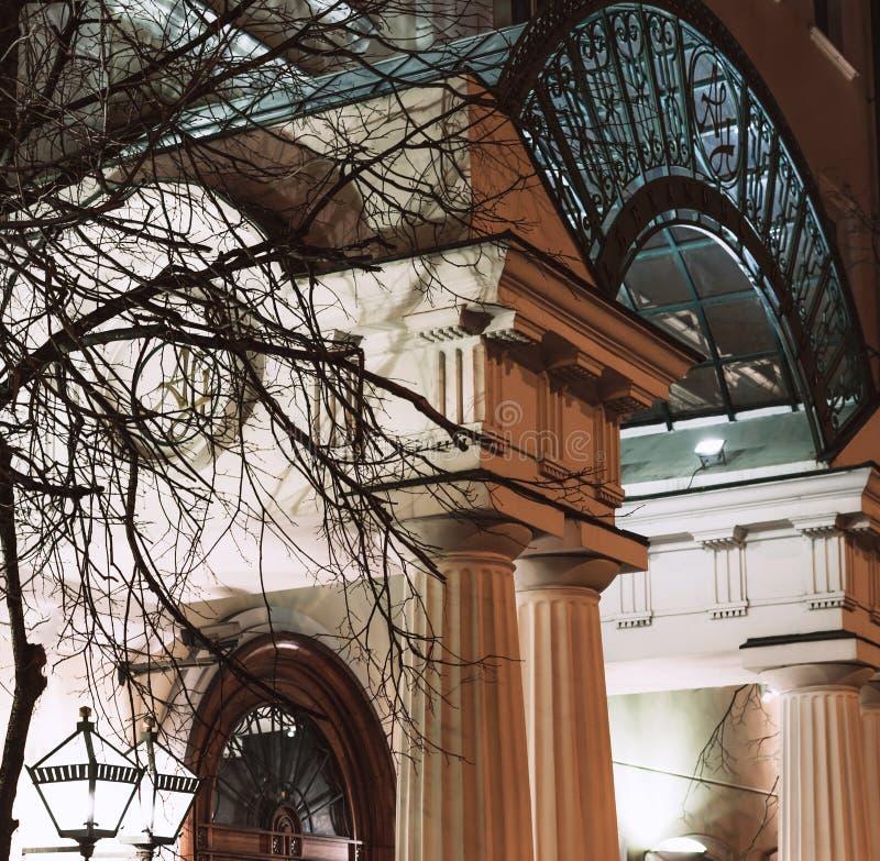Современный свод входа дома белого камня с освещенными фонариками вечером стоковое изображение