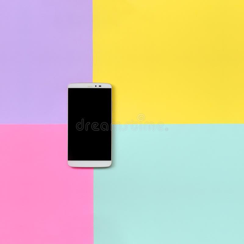 Современный смартфон с черным экраном на предпосылке текстуры голубой моды пастельной, желтой, фиолетовой и розовой бумаги цветов стоковые изображения rf