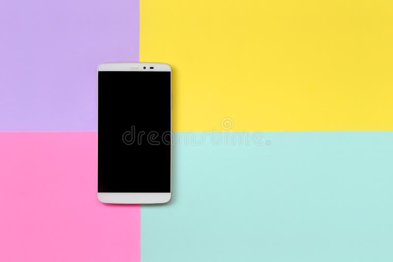 Современный смартфон с черным экраном на предпосылке текстуры голубой моды пастельной, желтой, фиолетовой и розовой бумаги цветов стоковое фото rf