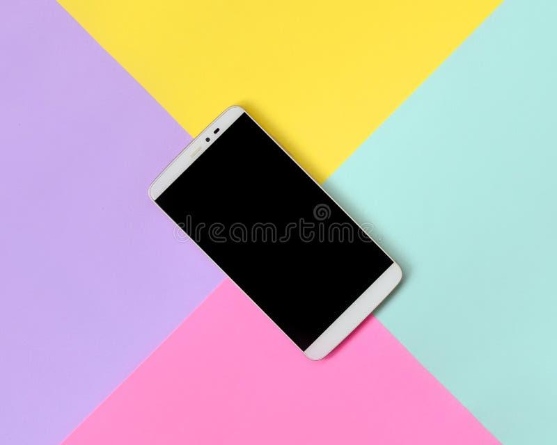 Современный смартфон с черным экраном на предпосылке текстуры голубой моды пастельной, желтой, фиолетовой и розовой бумаги цветов стоковые фото