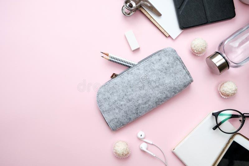 Современный стол места для работы женщины с тетрадью, телефоном, листом, карандашами, конфетой, кофе, водой, наушниками на розово стоковые изображения