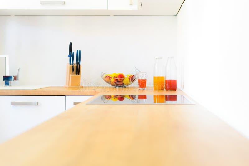 Современный счетчик кухни с hob индукции, свежими фруктами и домодельным лимонадом стоковое фото