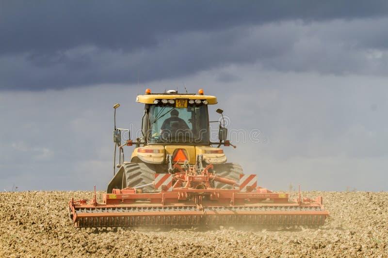 Современный трактор претендента культивируя английское поле урожая стоковая фотография rf