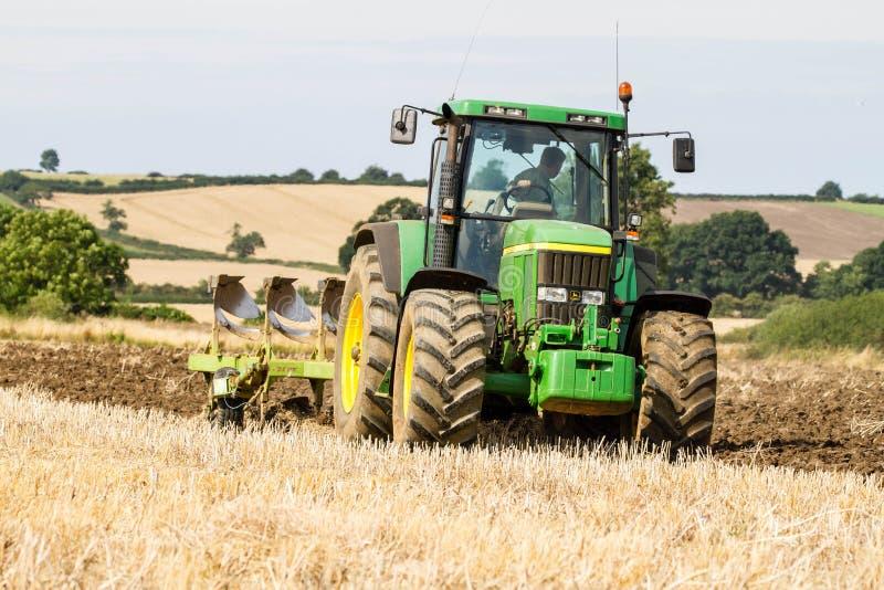 Современный трактор John Deere вытягивая плуг стоковые изображения rf