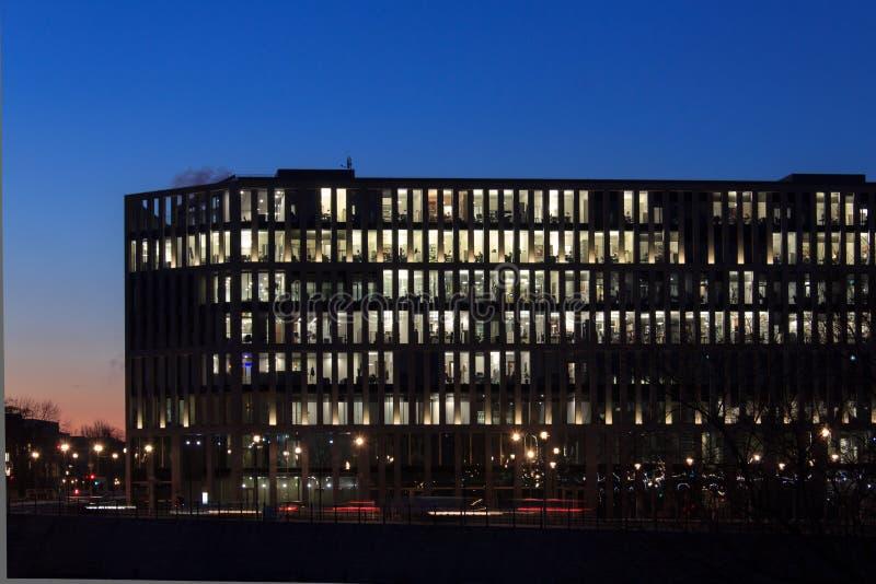 Современный фасад офисного здания, люди работая на ноче стоковое изображение